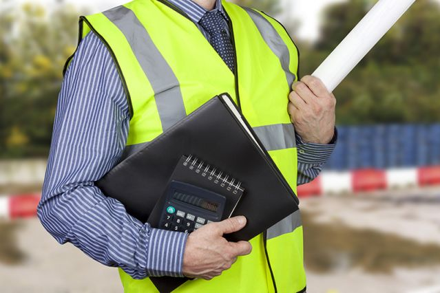 A surveyor with a file, a notepad and a calculator