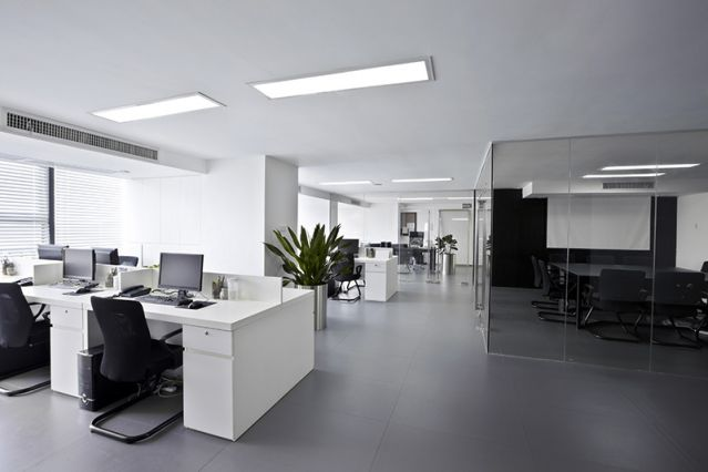 A brightly lit office environment, with air conditioning units built in to the ceiling